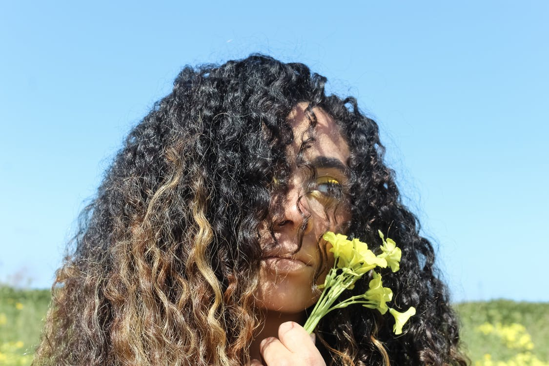 Portrait photo of curly hair woman holding flower
