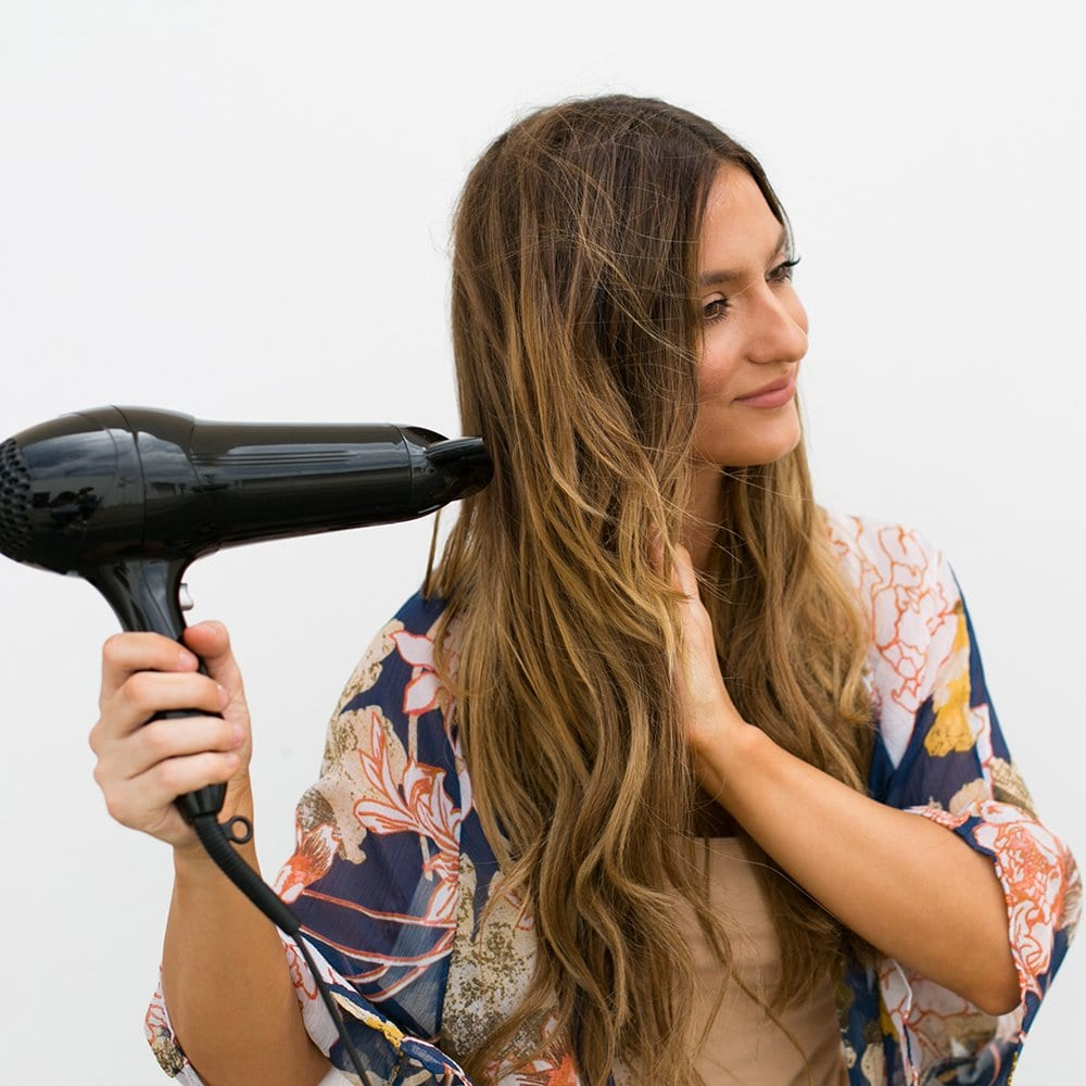 woman using a Revlon 1875W Quick Dry Lightweight Hair Dryer